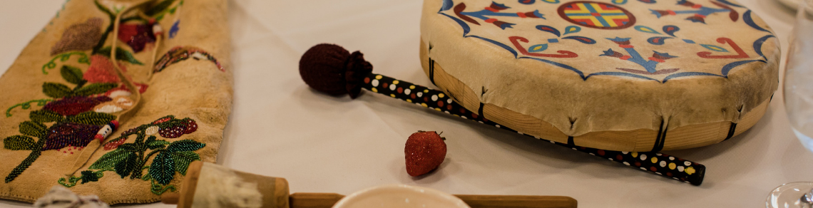 Indigenous artifacts and food, including drum, strawberry and beaded bag