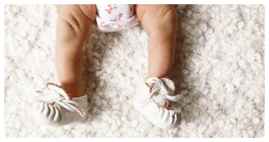 Indigenous baby, wearing traditional moccasins