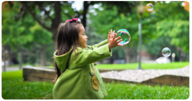Young toddler trying to capture a soap bubble