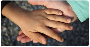 Hand of an adult and child clasping